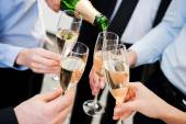 Business people holding flutes with champagne — Stock Photo