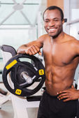 African man in gym near the bench press — Stock Photo