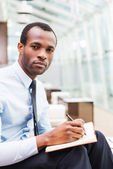 African man in formalwear writing in note pad — Stock Photo
