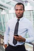 African man in shirt and tie holding mobile phone — Stock Photo