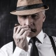 Man in hat and suspenders smelling cigar — Stock Photo #60363353
