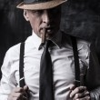 Senior man in hat smoking cigar — Stock Photo #60363471