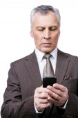 Mature man in formalwear holding mobile phone — Stock Photo