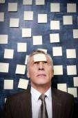 Man in formalwear with adhesive note on forehead — Stock Photo