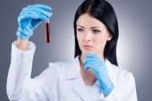 Female doctor holding flask with blood — Stock Photo