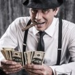 Gangster in shirt and suspenders counting money — Stock Photo #60758477