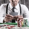 Serious senior man sitting at the poker table — Stock Photo #60758581