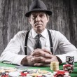 Senior man sitting at the poker table — Stock Photo #60758625