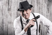 Man in gangster clothing holding gun — Stock Photo