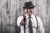 Man in gangster clothing stretching out  gun — Stock Photo