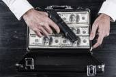 Man holding gun and briefcase full of currency — Stock Photo