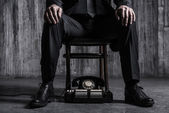 Man sitting at chair with old-fashioned telephone — Stock Photo