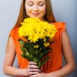 Woman in pretty dress holding bouquet of flowers — Stock Photo #61867609