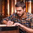 Young man in casual shirt writing in his note pad — Stock Photo #61925257