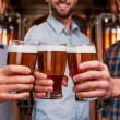 Young men stretching out glasses with beer — Stock Photo #61925325
