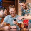 Men drinking beer in pub with smart phone — Stock Photo #61925525