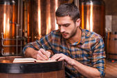 Young man in casual shirt writing in his note pad — Stock Photo