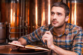 Thoughtful young man holding note pad — Stock Photo