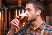 Brewer in apron tasting fresh beer — Stock Photo