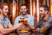 Young men in casual wear toasting with beer — Stock Photo