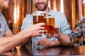 Young men toasting with beer  in  pub — Stock Photo