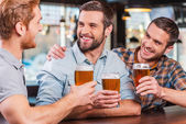 Young men talking and drinking beer — Stock Photo