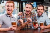 Men holding  beer and watching football match in bar — Stock Photo