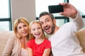 Happy family photographing them with smart phone — Stock Photo