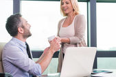 Woman giving cup of coffee to businessman — Stock Photo