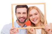 Loving couple looking through frame — Stock Photo