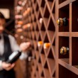 Wine shelves and male sommelier — Stock Photo #63946381
