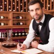 Sommelier writing in note pad — Stockfoto #64997945