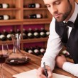 Sommelier writing in note pad — Stockfoto #64998005