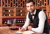 Sommelier writing in note pad — Stock Photo