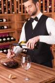 Sommelier pouring wine to decanter — Stock Photo