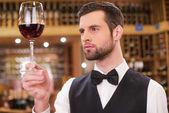Confident man examining red wine — Stock Photo
