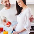 Woman cutting vegetables with her husband — Stock Photo #65729135