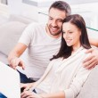Young loving couple looking at laptop — Stock Photo #65729837