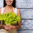 Young woman holding fresh lettuce — Stock Photo #65816583