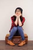 Woman in headwear sitting on suitcase — Stock Photo