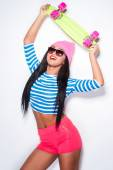African woman holding skateboard and smiling — Stock Photo