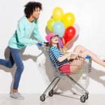 Boy carrying his girlfriend in shopping cart — Stock Photo #67653425