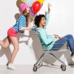 Girl carrying his boyfriend in shopping cart — Stock Photo #67653441