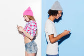 Young couple holding mobile phones — Stock Photo