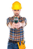 Young male carpenter stretching out drill — Stock Photo