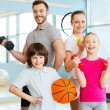Family holding different sports equipment — Stock Photo #68200921