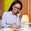 African woman making notes in note pad — Stock Photo #68876943