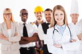When I grow up I will be a doctor. Beautiful young female doctor keeping arms crossed and smiling while group of people in different professions standing in the background — Stock Photo