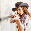 Cowgirl aiming her gun at camera — Stock Photo #71395457