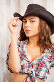Cowgirl adjusting her hat — 图库照片